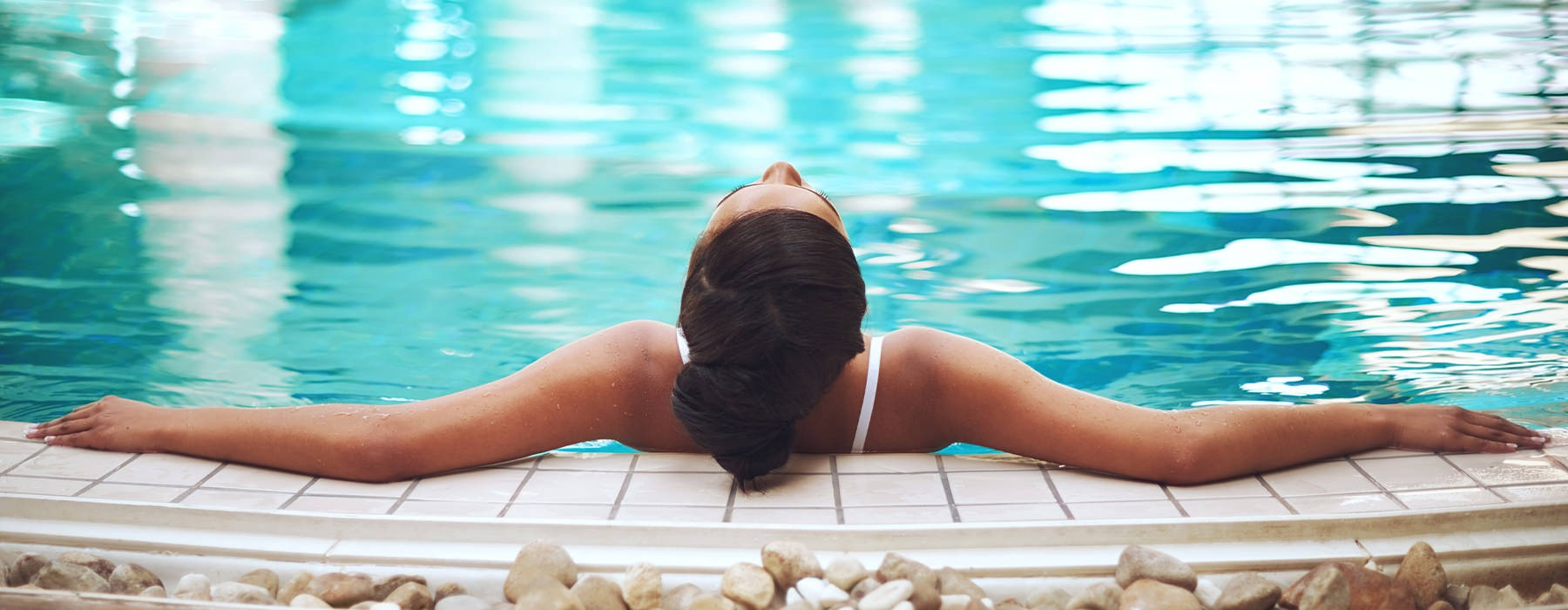 Woman lounging in a sparkling blue swimming pool