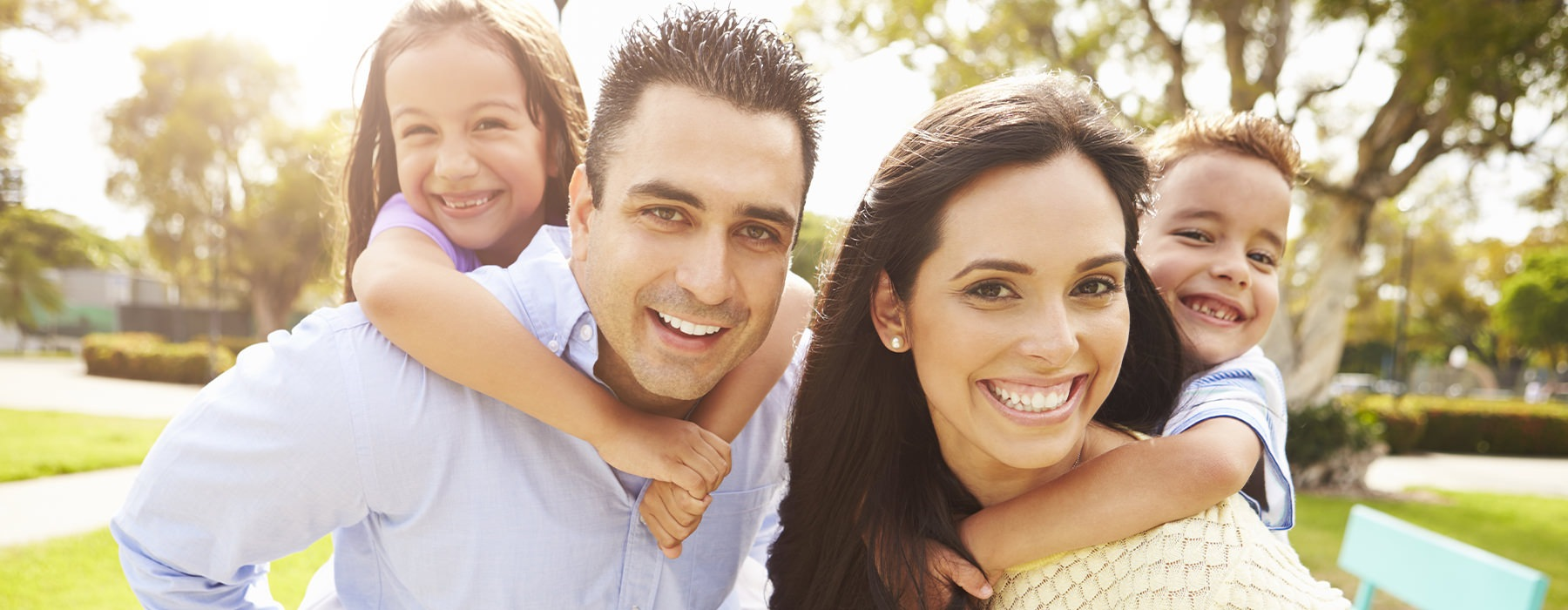 Family of four outside smiling